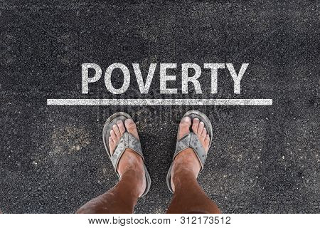 Poverty. Man With Dirty Feet In Slippers Is Standing On Asphalt Next To Line And Word Poverty