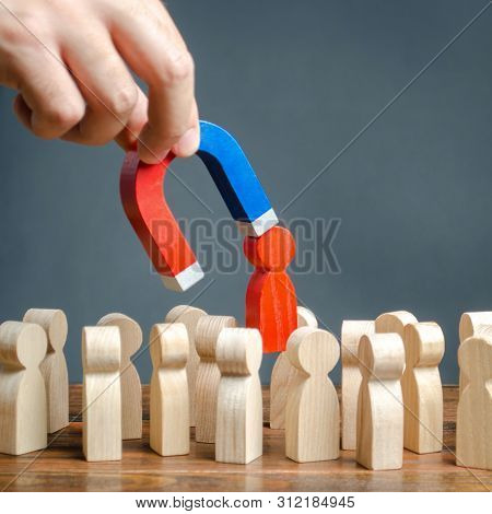 The Hand With A Magnet Pulls Out A Red Figure Of A Man From The Crowd. Increase Team Efficiency, Pro