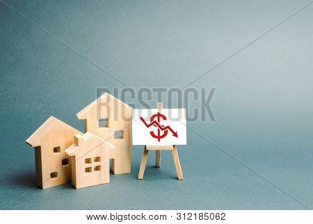 Three Wooden Houses With A Stand With Red Dollar Sign And Arrow Down. Concept Of Real Estate Value D