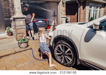 Cute Preschool Little Caucasian Girl Helping Father Wash Car On Driveway In Front House On Summer Da
