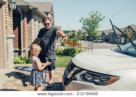 Cute Preschool Little Caucasian Girl Child Helping Father Wash Car With Water From Hose On Driveway