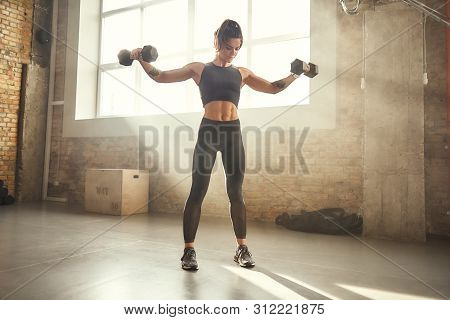 Perfect Body. Young Athletic Woman In Sportswear Exercising With Dumbbells While Standing In Front O
