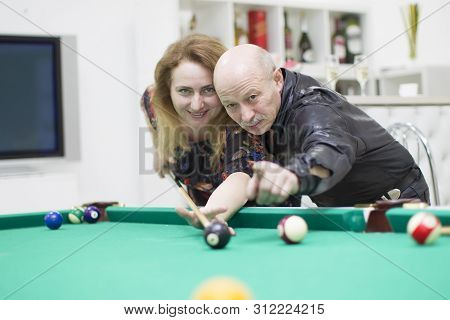 An Elderly Man With A Woman Playing Billiards. Late Love. Pensioner Flirts With A Girl.gray Hair In