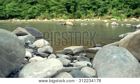 Time Lapse. Splash Of Water In A Mountain River Near The Mountain Forest. View Of The Water Between