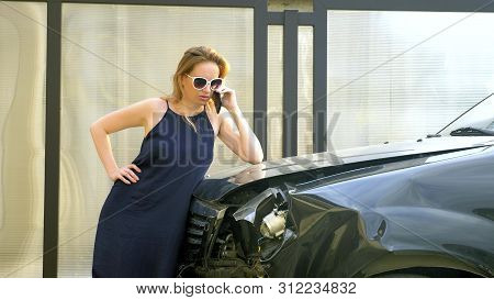 Car Accident Concept. Woman In A State Of Shock Talking On The Phone After A Car Accident, Standing