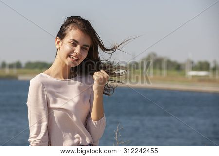 Cheerful Girl Making Gun Shot Gesture. Beautiful Young Woman In Casual Enjoying Leisure Time In City