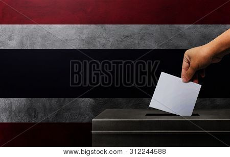 Hand Holding Ballot Paper For Election Vote At Thailand National Flag Background. Thailand Voting Co