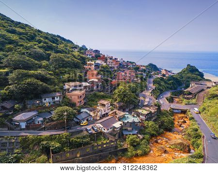 Aerial View Of Buildings In Jiufen Village On Mountain Hill With Sea And Green Natural Forest Trees