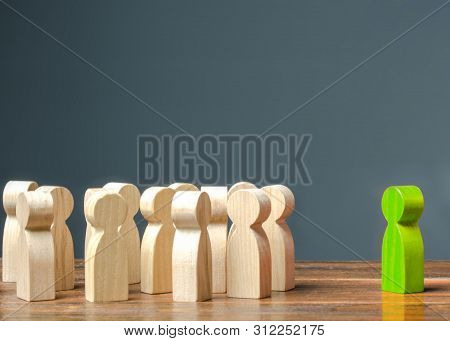 Green Figurine Of A Man Stands Near The Crowd Of People. Development Of Leadership And Social Qualit