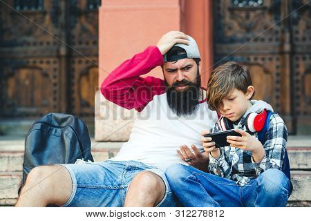 Father and son are using smartphones. Dad and son spending time together outdoors. Teen boy playing games on phone. Fatherhood and family relationship. poster