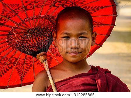 Bagan, Myanmar - Feb 17, 2016. Portrait Of Buddhist Novice With Umbrella In Bagan, Myanmar. Bagan Is