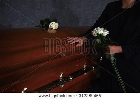 Young Woman With White Roses Near Casket In Funeral Home, Closeup