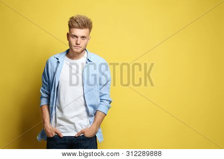 Young Man Wearing Blank T-shirt On Yellow Background. Mockup For Design