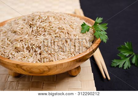 Brown unpolished rice in a wooden bowl on a slate background. Selective focus. poster
