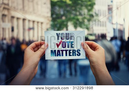 Hands Hold A Paper Sheet With The Message Your Vote Matters Over A Crowded Street Background. People