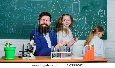 Fascinating biology lesson. School teacher of biology. Man bearded teacher work with microscope and test tubes in biology classroom. How to interest children study. Explaining biology to children poster