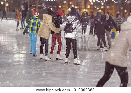 Group Of Girls Skating Back To Us. Girlfriends Ice Skating In City Park, Snowy Evening. Healthy Outd