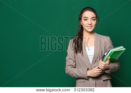Portrait Of Beautiful Young Teacher With Books Near Chalkboard, Space For Text