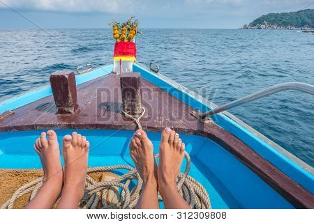 feet of child and mom at the traditional thailand longtail boat at the sea