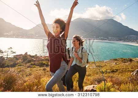 Millennial African American woman hiking by the coast with a friend celebrates reaching summit