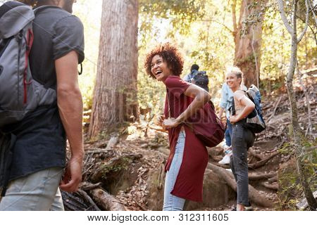 Millennials hiking up a forest trail turning around to look back at friends, three quarter length