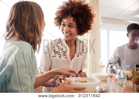 Two millennial girlfriends talking at the table during lunch with friends, close up