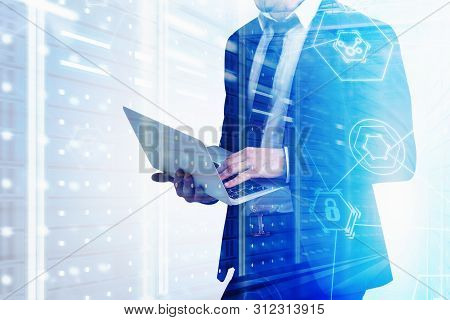 Unrecognizable Man In Suit Working With Laptop In Server Room With Double Exposure Of Cyber Security