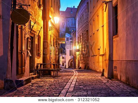 Narrow street of Old town with Night illumination. Czech Krumlov. Czech Republic. Shining lanterns at walls of medieval houses and road of paving stones.
