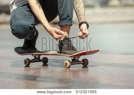 Skateboarder Preparing For Riding At The Citys Street In Sunny Day. Young Man In Sneakers And Cap Wi
