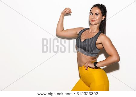 Image of beautiful pleased amazing young sports fitness woman isolated over white wall background showing biceps.