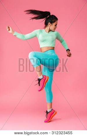 Picture of amazing concentrated young sports fitness woman isolated over pink wall background make exercises.