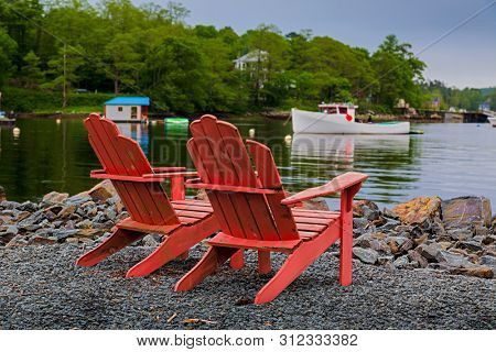 Two Adirondack chairs on the rocky shore of the south shore of Nova Scotia, Canada.