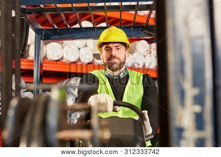 Worker as forklift driver on the forklift in the forwarding warehouse