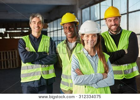 Logistics worker team with crossed arms in an industrial warehouse