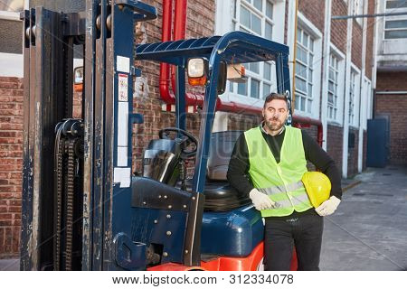Man as forklift driver with forklift in front of the warehouse in the logistics center