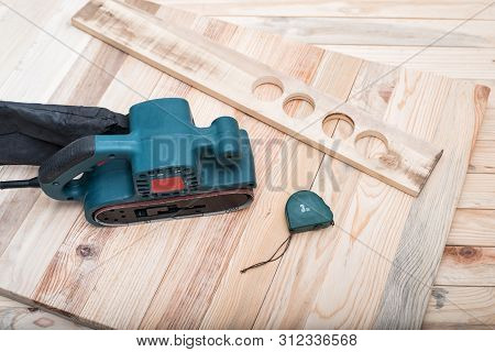 Electric belt sander, measuring tape and workpiece lying on a light brown wooden table. Woodworking, sanding machine poster