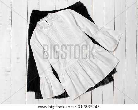 White Blouse On Black Skirt. Wooden Background. Fashionable Concept