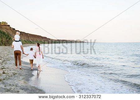 Family Of Four Walking Along The Seashore. Parents And Two Sons. Back View