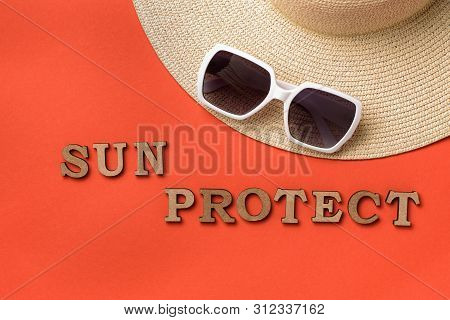 Word Sun Protect From Wooden Letters. Sun Glasses And A Hat. Live Coral Background. Travel Concept