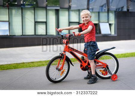 Blond Boy On A Children's Bicycle. Urban Background