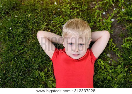 Portrait Of A Blond Boy Lying On The Grass. Hands Behind Head. Rest At Nature