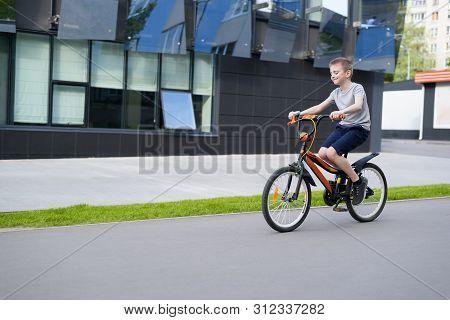 Schoolboy Rides A Bicycle. Summer Holidays. Urban Background