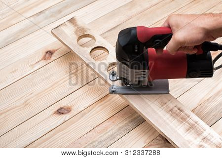 Electric Jigsaw In Male Hand. Processing Of Workpiece On Light Brown Wooden Table