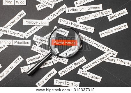 Magnifier Glass Over The Red Inscription Power Words Cut Out Of Paper. Surrounded By Other Inscripti