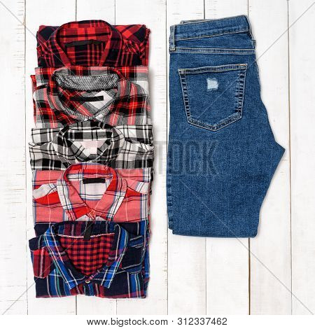 Plaid Shirts And Blue Jeans On A White Wooden Background. Clothing Concept. Top View