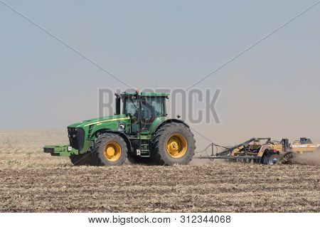 Primorsk, Ukraine - August 15, 2018: Tractor Plowing The Ground Against The Blue Sky.