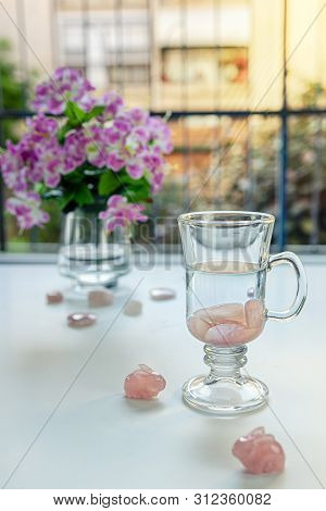 In Irish coffee mug preparing drinkable gem elixir. Burnished rose quartz stones are placed into distilled water. Two stone rabbits sit nearby it. Vase with flowers is seen on the balcony table. poster