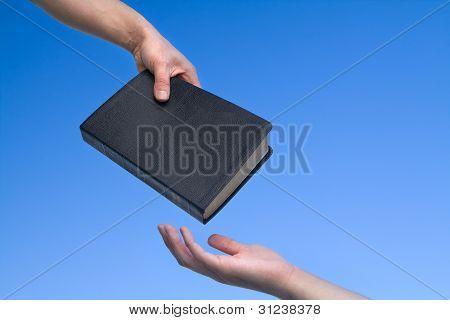 Hand Giving Bible