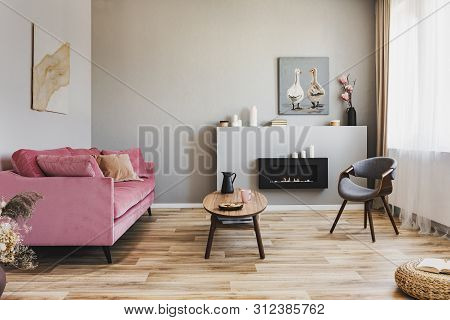 Stylish Living Room Interior With Pastel Pink Sofa, Wooden Coffee Table And Eco Fireplace