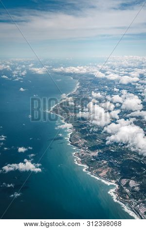 Flight Over The Coast Of Portugal Lissabon Region . Aerial View Through The Airplane Window With Clo